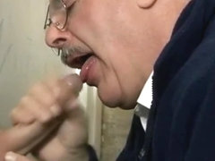 Grey old moustached man giving blowjob through glory hole