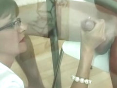 Cuckold watches wife give tugjob through glass table