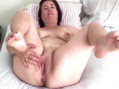 Pregnant mature mom on the bed spreading legs